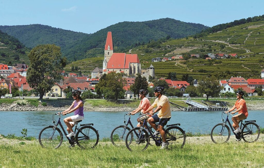 Golf Ahoy Danube River Golf Cruise AmaMagna four guests cycling on bank of danube river
