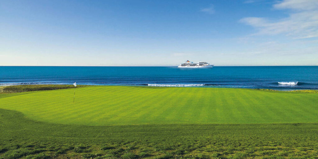 photo of golf greens with cruise ship in back ground