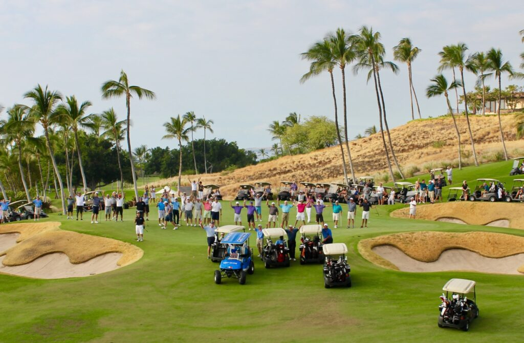 group of corporate meeting delegates on golf course with electric golf carts