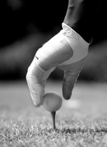 Golfer placing golf ball on tee showing gloved hand