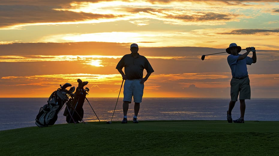 GolfAhoy Hawaii Golf Cruises photo view at sunset showing two golfers with brilliant pacific sunset in the background.