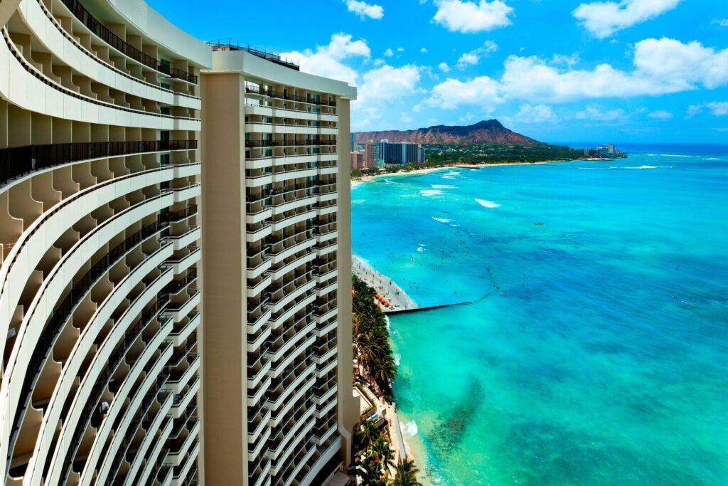 GolfAhoy Hawaii Golf Cruises exterior view photo of Sheraton Waikiki Beach with Diamond Head in the background.